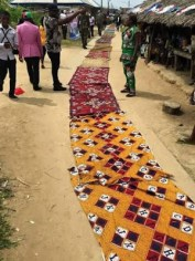 Bayelsa women lay their wrappers on the road for Governor Dickson to walk on.