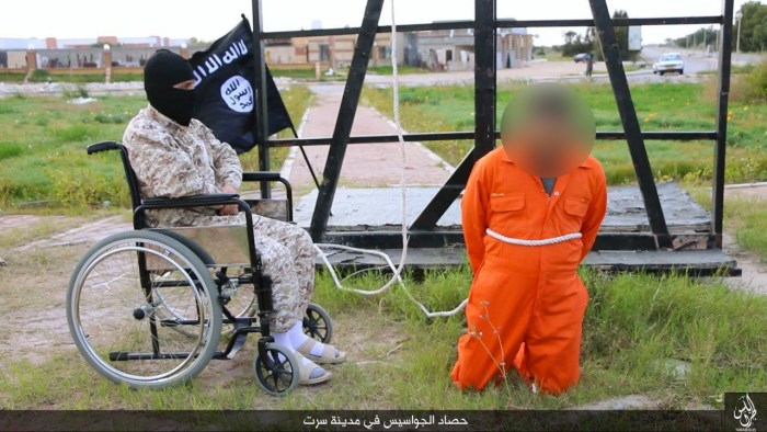 """ISIS Propaganda: The wheelchair-bound militant sits next to an alleged """"spy"""" before he is lifted up by a rope and crucified.   Wilayat Tarabulus"""