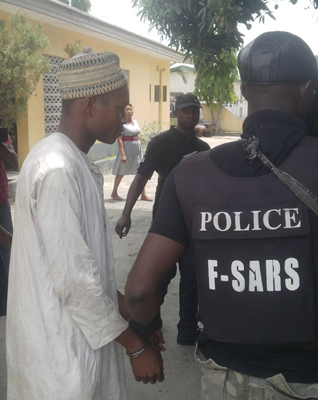 The accused, Yunusa 'Yellow' (in handcuffs) being led by a police officer to a Federal High Court in Yenagoa | Vanguard