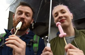 A couple hold candy in the shape of phalluses at the Wakamiya Hachimangu Shrine during the Kanamara Festival in Kawasaki, a suburb of Tokyo on Sunday, April 3, 2016.
