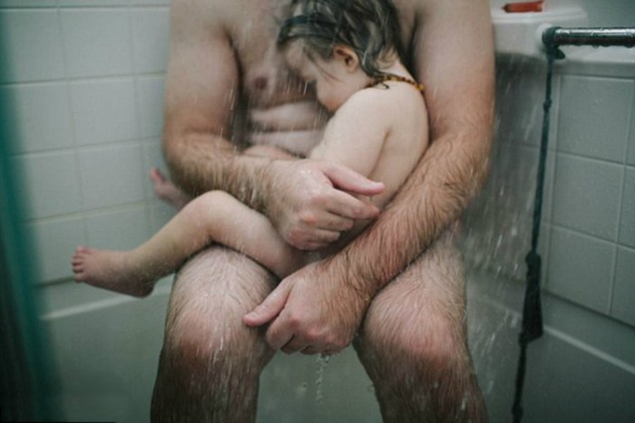Photographer Heather Whitten shared the naked photo of her husband, Thomas cradling their son in the shower | Heather Whitten