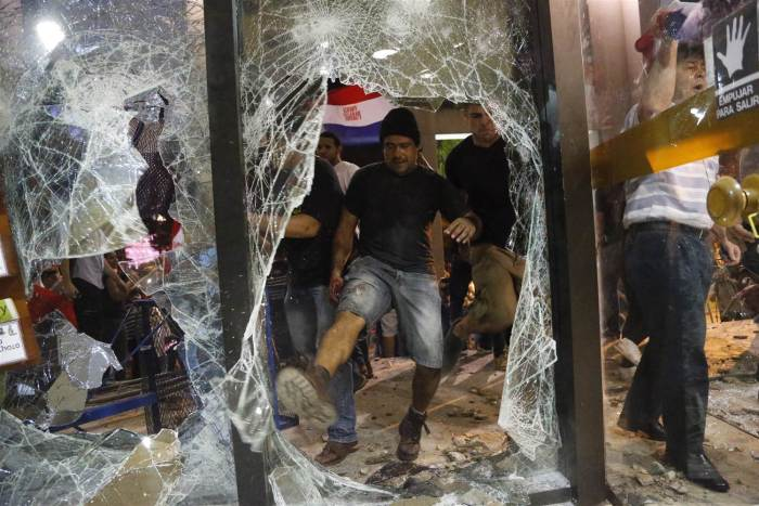 Paraguay: A man kicks at a shattered