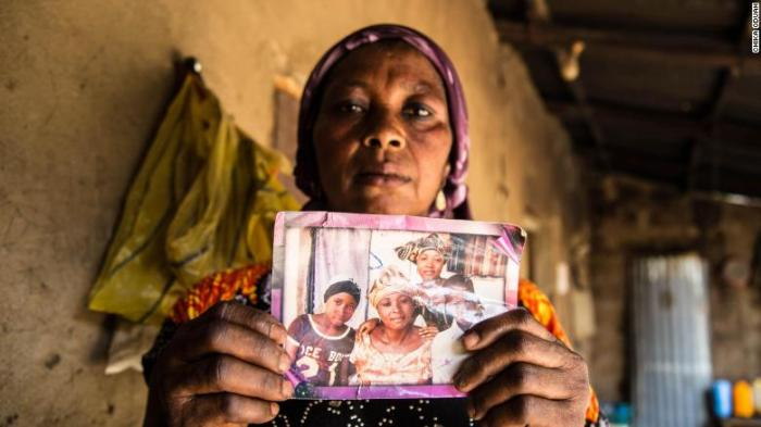 Rebecca Sharibu holds up a photograph that shows her daughter Leah, seated on the left in a black shirt. Leah was kidnapped in February 2018 from her school in the town of Dapchi in northern Nigeria by members of the terrorist organization Boko Haram. Photo by Chika Oduah. April 2018.