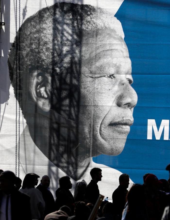 People gather below a giant banner of the late Nelson Mandela (Themba Hadebe/AP)