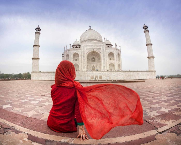 Woman in red costume with flattering scarf sitting near Taj Mahal in Agra, Uttar Pradesh, India