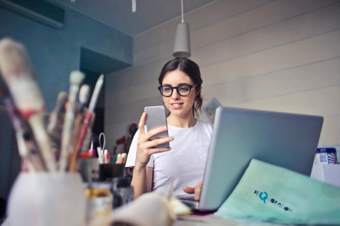 woman desk office phone smartphone laptop