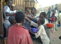 A group of Almajiri children struggling for alms given them by a trader in Northern Nigeria