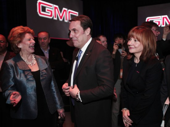 Mary Barra with Mark Reuss and some laughing rando at the GMC Eminence Front booth during the 2015 Detroit Auto Show