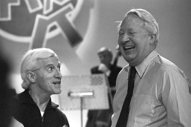 Savile and the former prime minister Edward Heath share a joke at BBC rehearsals in 1980