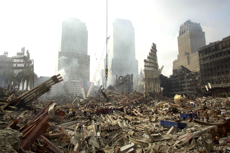 """Rescue workers sift through debris at the scene of what was once the plaza area of the World Trade Center twin towers, September 24, 2001. It would take a """"miracle"""" to find anyone alive in the ruins of the World Trade Center and relatives of more than 6,000 missing people would soon be able to apply for death certificates, Mayor Rudy  Giuliani said on Monday. REUTERS/John Roca/New York Daily News/pool HK - RTRN8RF"""