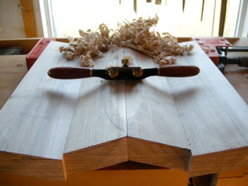 Start with a spokeshave and begin removing the center waste material.