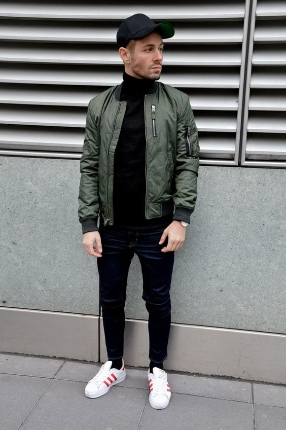 Green-Bomber-Jacket-styled-with-Black-Sweater-Denim-Jeans-and-round-off-this-look-by-wearing-White-Sneakers-1