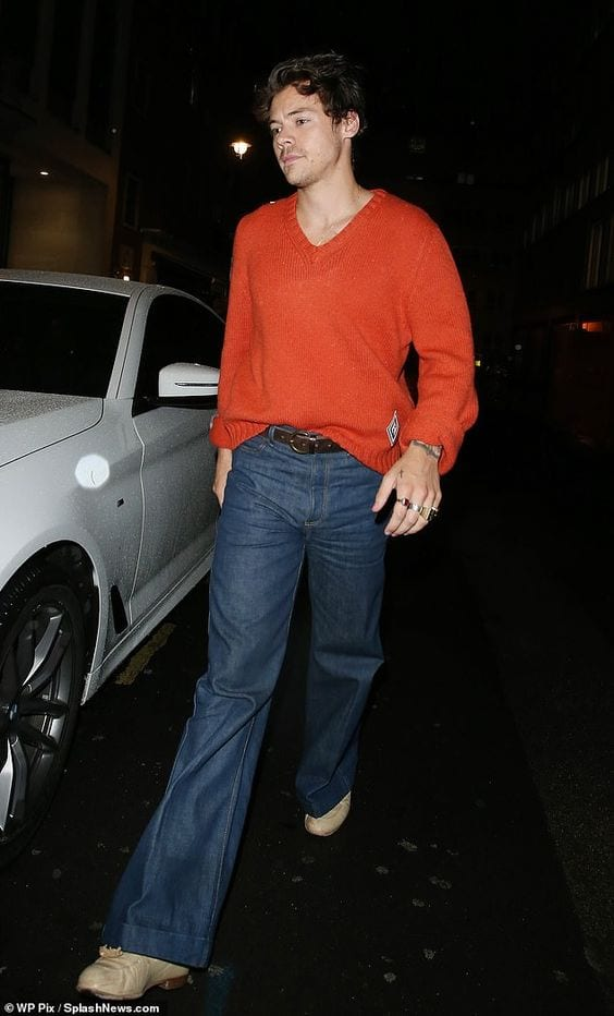 Harry Styles wearing the classic flared jeans and sweater outfit