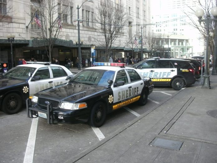 Several sheriff vehicles park on Pine Street in Downtown Seattle next to the light rail station.