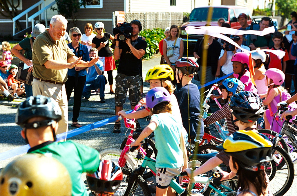 Mayor Mike McGinn cutting the ribbon on the Ballard Neighborhood Greenway as kids on bikes line up to get a first ride. (Credit: Dennis Bratland)