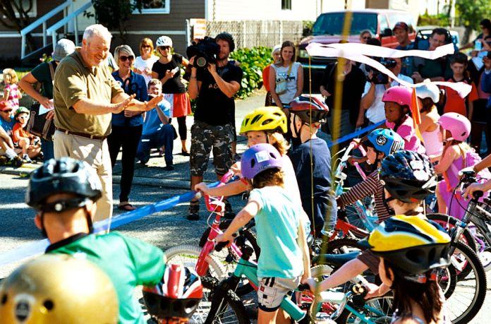 Mayor Mike McGinn cutting the ribbon on the Ballard Neighborhood Greenway as kids on bikes line up to get a first ride. (Credit: Dennis Bratland)