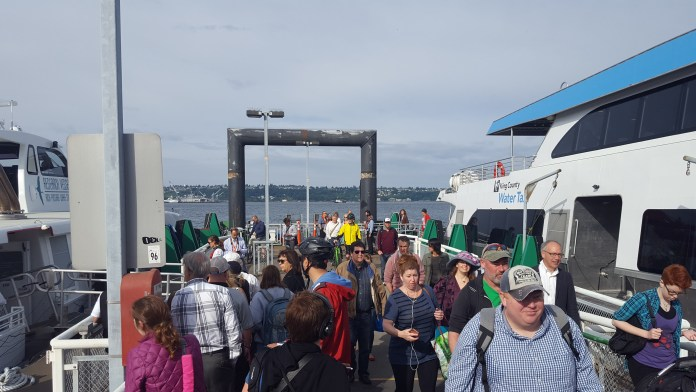 Passengers on Colman Dock with a ferry docked.