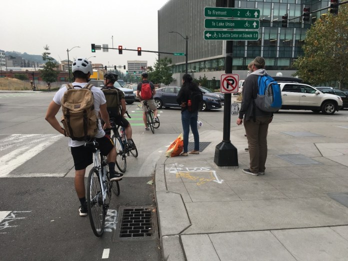 Three people biking and two pedestrians wait for a long line of cars queuing on Mercer Street in South Lake Union.