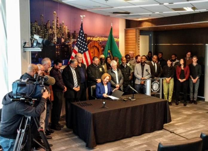 Mayor Jenny Durkan signs the Fare Share Plan into law at city hall. (Photo by author)