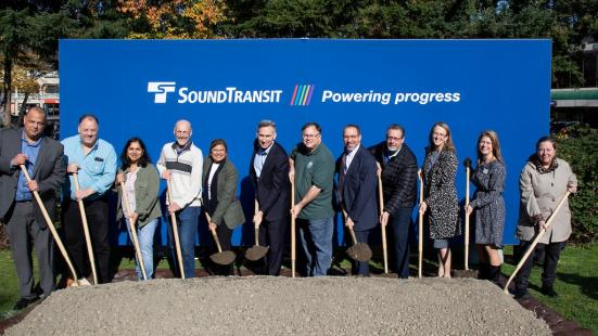 12 officials exercise their shovel arms in this posed photo for the groundbreaking for the Downtown Redmond Link Extension. (Sound Transit)
