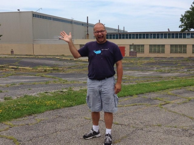 Waving goofball standing in the empty parking lot of a factory.