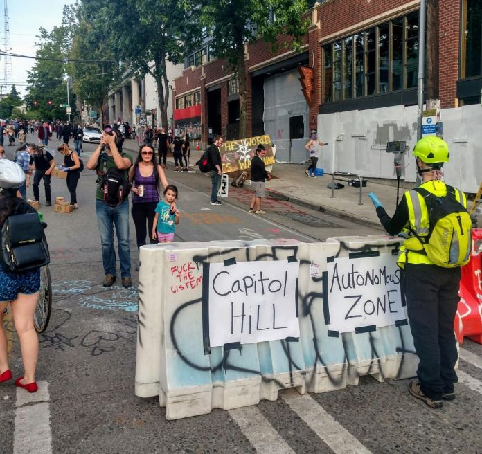 """People snap pictures and wander around surrounded by street art. A construction barrier that announces """"Capitol Hill Autonomous Zone"""" (Photo by Doug Trumm)"""