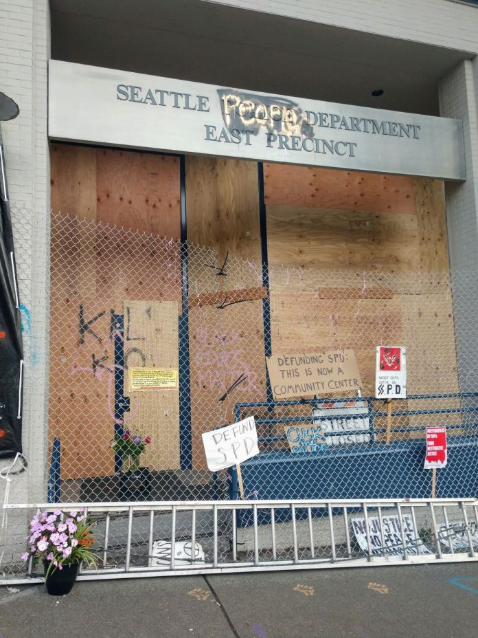 """Sign outside Seattle People's Department reads """"Defunding SPD: This is now a community center."""" (Photo by Doug Trumm)"""