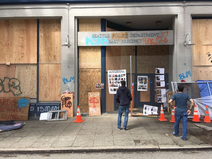 "The East Precinct is boarded up and protesters have added some edits to signage such as ""Fuck 12"". (Photo by Michael Goldman)"