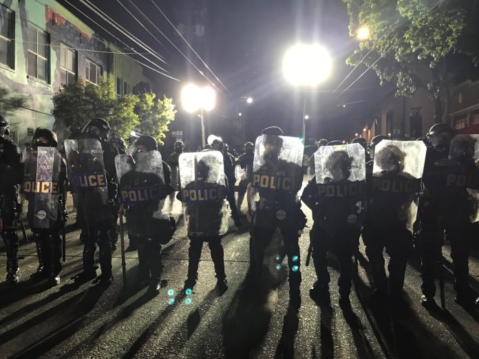 A wall of police with riot shields outside East Precinct.