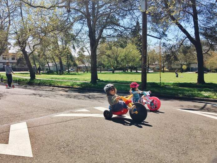 Two young kids on trikes in an open street.