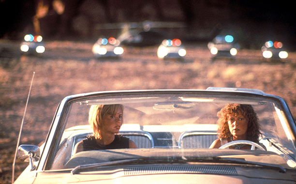Thelm and Louise in a white convertible with cope cars in the background in the iconic scene from the 1991 film.