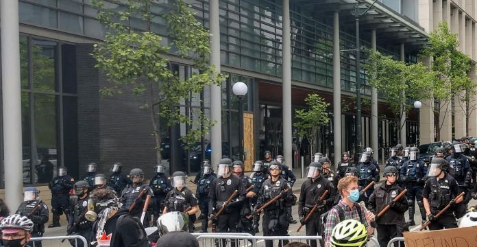 Police hold nightsticks in full riot gear behind a metal fence as protesters march by.