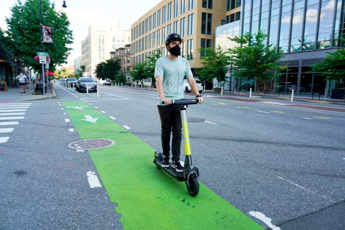 Man riding a LINK scooter in a green bike lane in South Lake Union