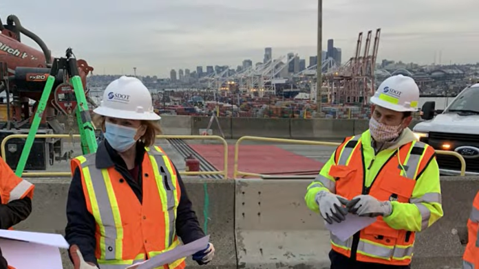 Mayor Durkan in an orange vest and SDOT hard hat at a West Seattle Bridge presser.
