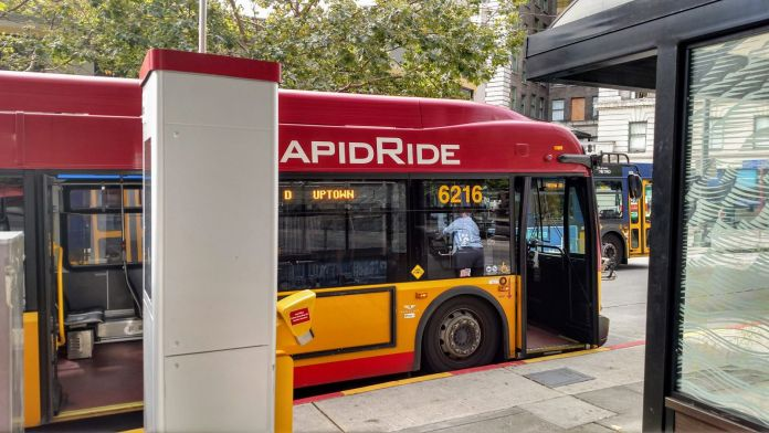 A red RapidRide bus at a stop with a off-board payment kiosk and bus shelter.