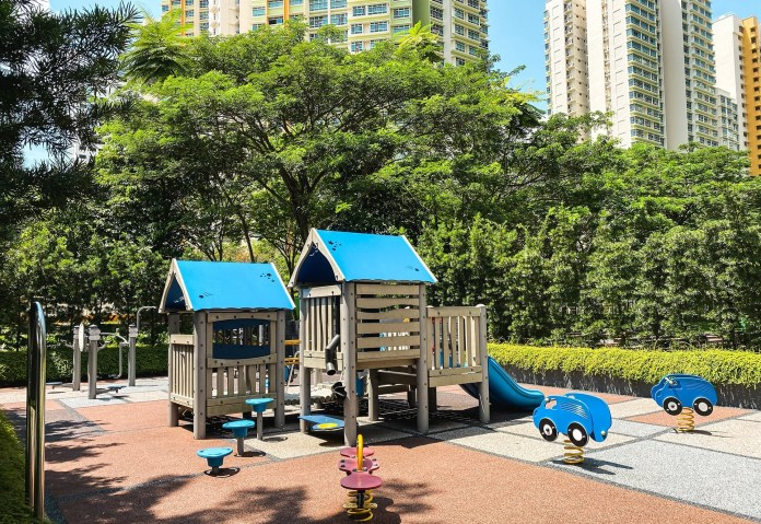 A playground with trees and public housing towers in the background