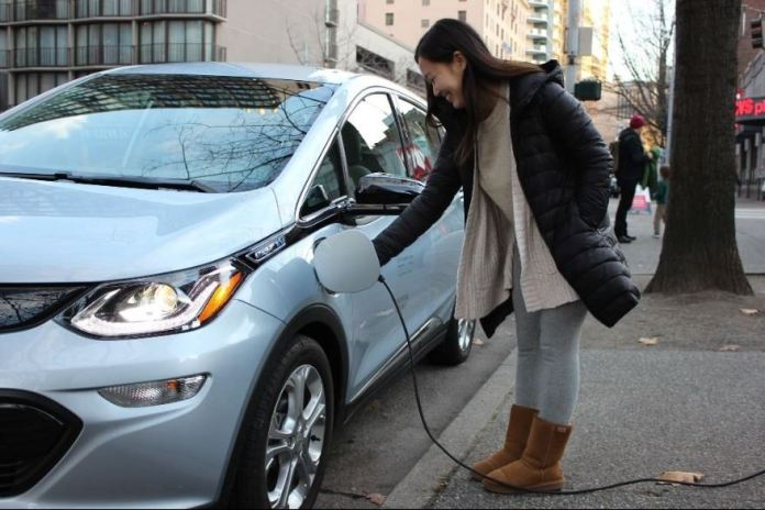 A women charges an electric sedan.