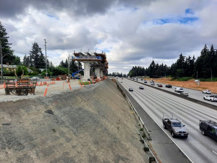 A light rail guideway rises on the edge of a freeway trench at the 130th Street overpass.