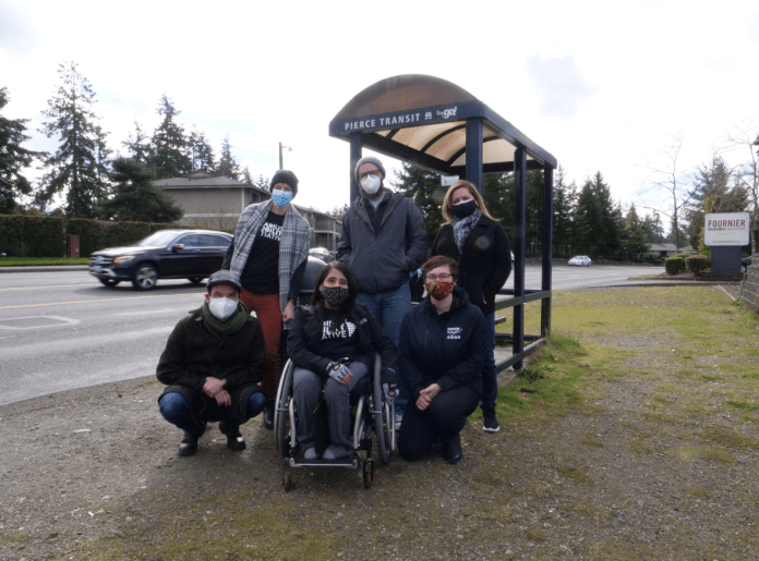 A woman in a wheelchair and five other advocates at a Tacoma bus stop.