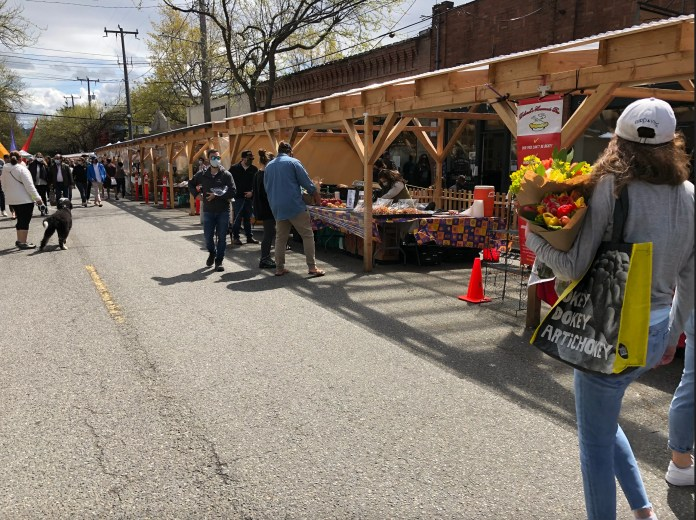 Wooden pergolas on Ballard Ave have farmers market booths set up in them.