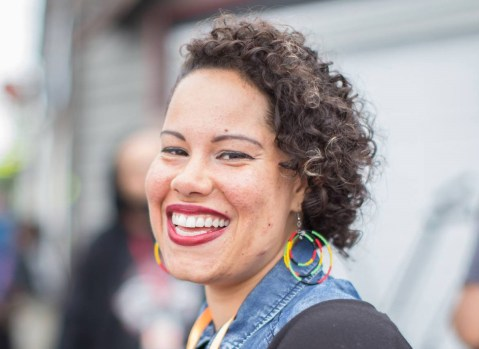 Nikkita is a Black woman. She wears rainbow hoop earrings. her curly hair to the side, and a big smile.
