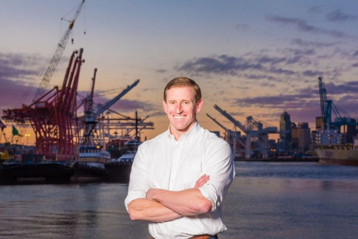 Ryan calkins stands in front of cranes on the Seattle waterfront.