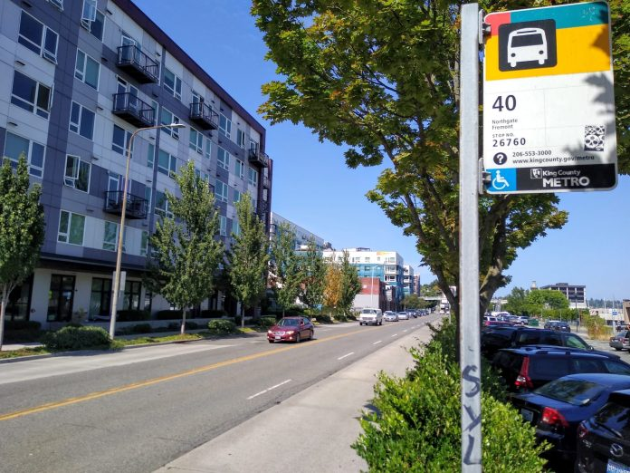 A bus stop along a four lane busy road reading