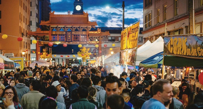 A crowded Chinatown-International District Night Market with a view of the Chinatown gate near the King Street station.
