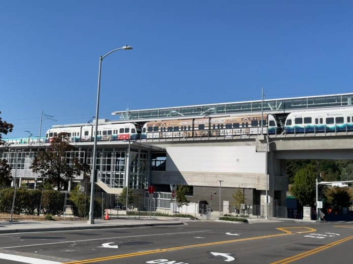 A photo of an elevated Link light rail line over a street.