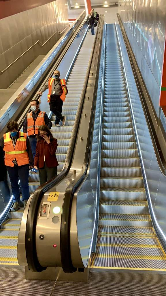 A photo looks up at a long, steep set of escalators that lead into the station. People wearing orange safety vests and a woman in a red coat ride the escalator.
