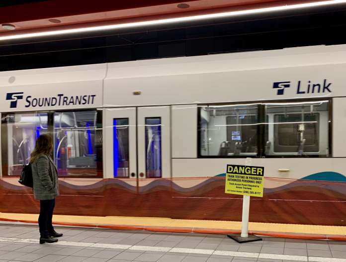 A woman stands in front of an empty Link light rail train. A yellow danger sign warns people that testing is in progress.
