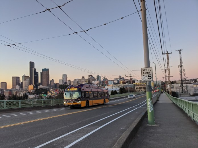 A photo shows a bike lane under construction on 12th Avenue at Jose Rizal Bridge. A King County Metro bus is driving on the bridge and the skyline of Downtown Seattle appears in the background.