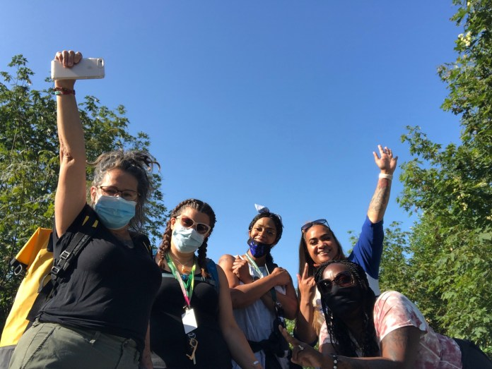 Five women wearing face masks raise their arms triumphantly in the air. They are standing outside with a blue sky behind them.
