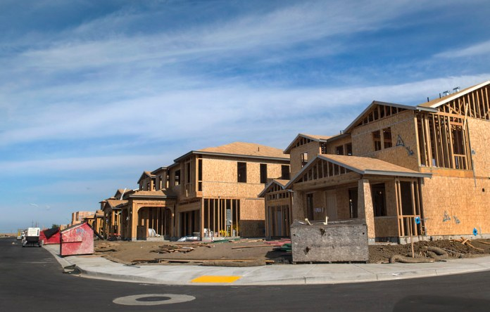 The photograph shows a curved street of a large two story houses with garages under construction